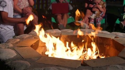 Group of people sitting on patio loungers around stone fire pit in back yard close-up