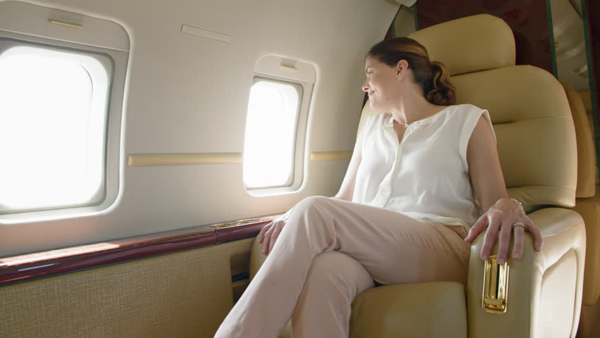 Attractive brunette woman in a white blouse and khaki pants waves through the window while relaxing in the cabin of an executive jet.  Wide shot, slow motion, originally recorded in 4K at 60fps.