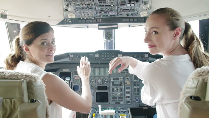 Two attractive brunette women high five each other, then turn to camera and smile while sitting in the cockpit of an executive jet. Mid shot, hand held, originally recorded in slow motion 4K at 60fps