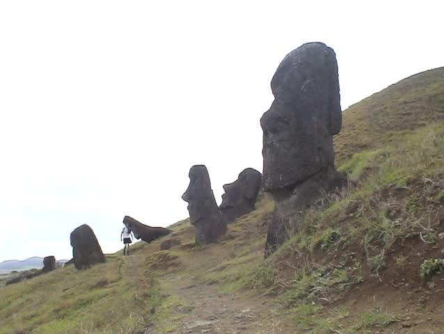 Person walking among ancient Moai Statues on the volcanic slope of Rano Raraku, on Easter Island, South Pacific.