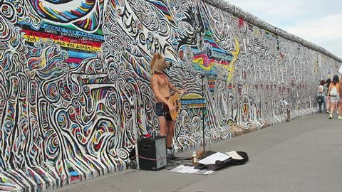 BERLIN, GERMANY - JULY 2015: Man with horse head is playing guitar at the Berlin Wall, Germany