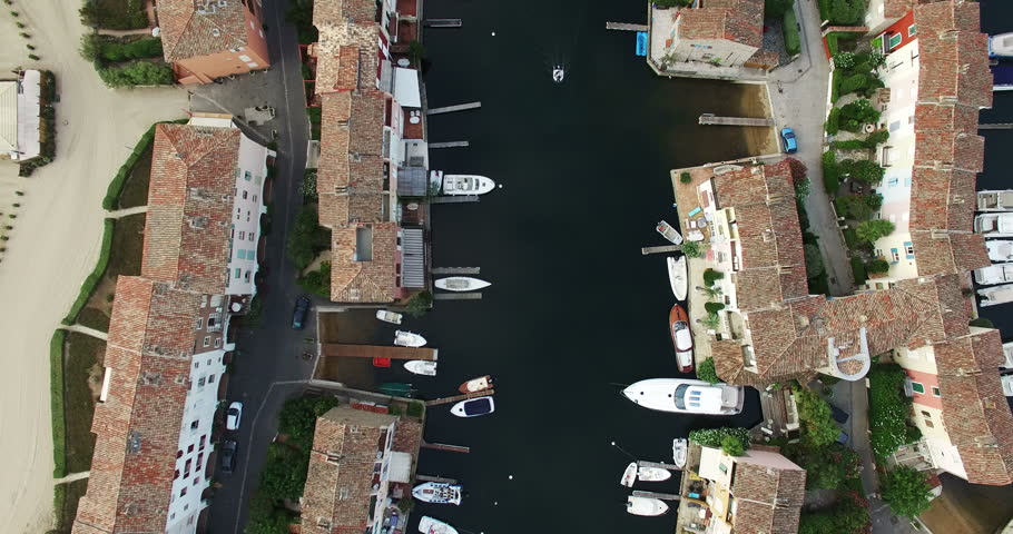 2015 High Quality Aerial Video (Ultra HD) of a small boat passing by in Port Grimaud in the French Riviera near St. Tropez. Looking down on the typical rooftops. Camera on a 90 degrees angle rotating.
