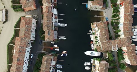 HQ Aerial Drone Video (Ultra HD) of a small boat passing by in Port Grimaud in the French Riviera near St. Tropez. Looking down on the typical rooftops. Camera on a 90 degrees angle rotating.