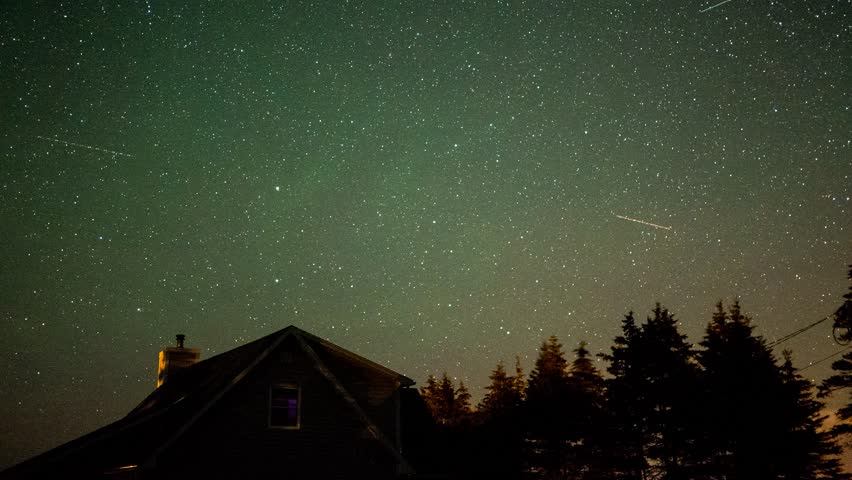A time-lapse of stars rotating above a house at night