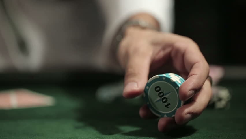 Casino: Man playing poker, excited, turns casino tokens in hand. Close up, slow motion