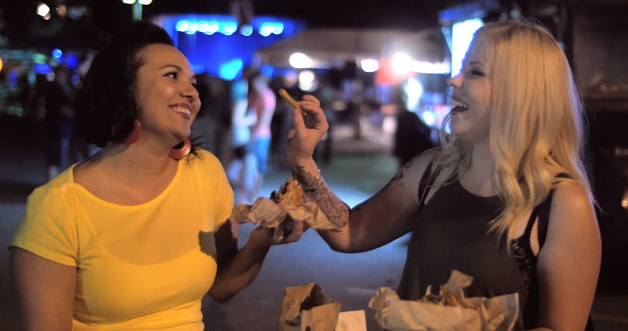4K A hip trendy woman jokes around and offers friend a bite of her delicious street food truck french fries in a urban outdoor music festival night setting.