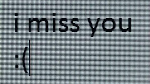""" i miss you :( "" being typed on computer screen in close up so that individual pixels can be seen."