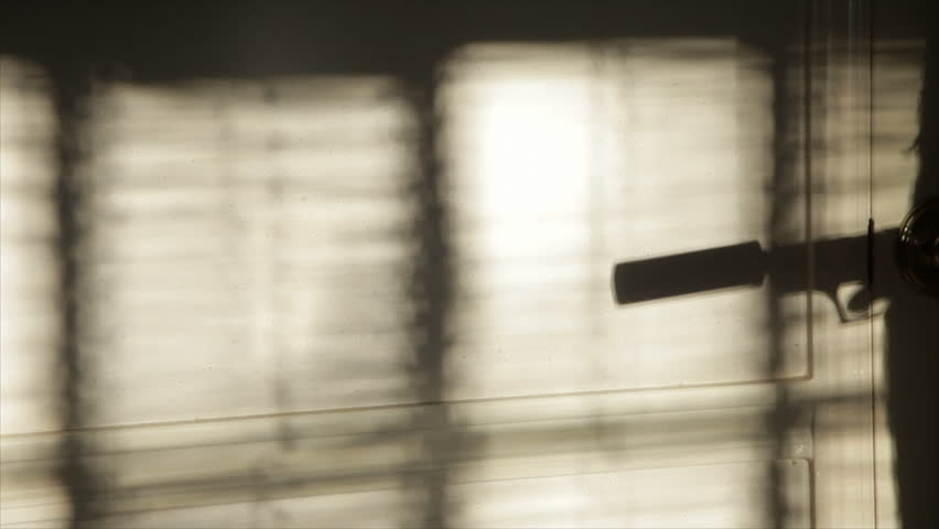 The evening or morning sunlight through window blinds captures the silhouetted firing of a pistol with a silencer attached to it. Blaze and smoke added to gun action in post.