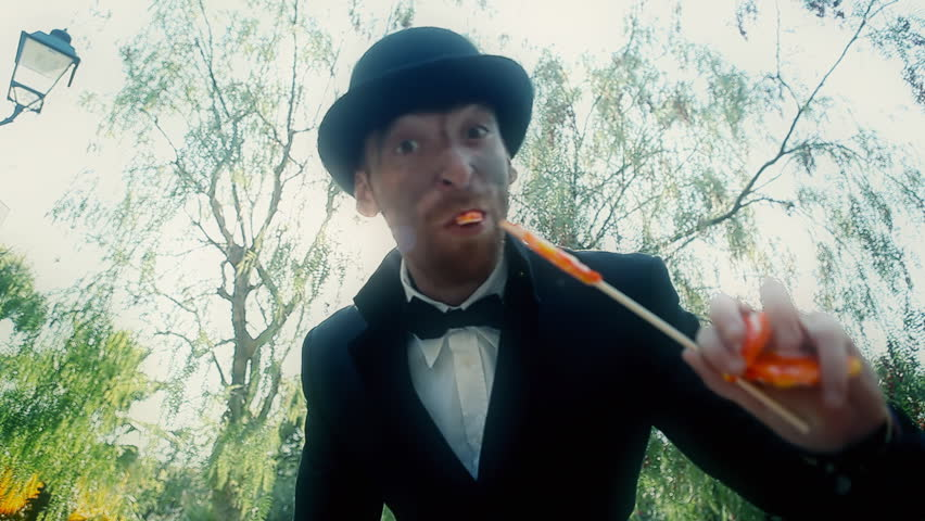 An evil man (a caricature) smashes a lollipop with his teeth, in front of a kid, while laughing. Kid's point of view. Funny grotesque scene.  | Shutterstock HD Video #11400626