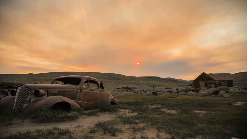 Hazy Sunrise Timelapse Over Abandoned Desert Town and Car