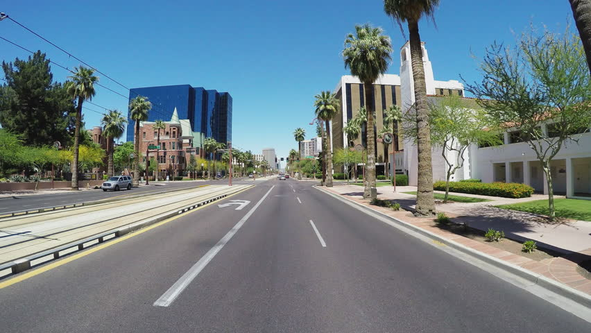PHOENIX, AZ/USA - June 27, 2015: Point of view driving vehicle shot of Phoenix Arizona city streets downtown. A driver passes by new buildings in business district.