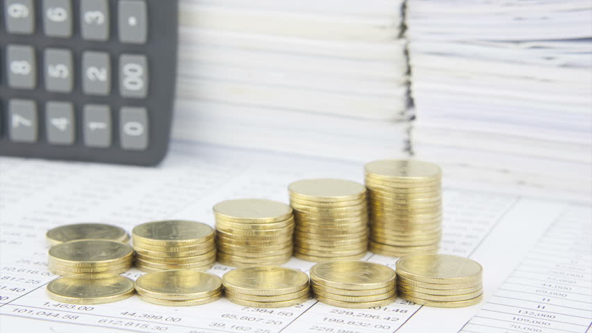 Different step pile of gold coins on finance account with calculator and stack old paper report of sales and receipt as background time lapse as work going to be successful. Business concept footage. | Shutterstock HD Video #11453900