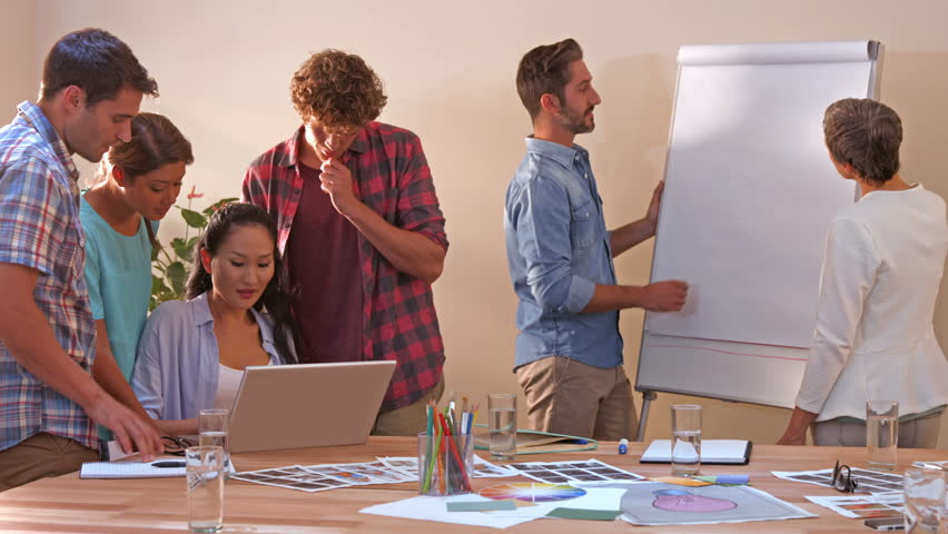 Creative business team working on laptop while their colleagues looking at white board in office | Shutterstock HD Video #11456456