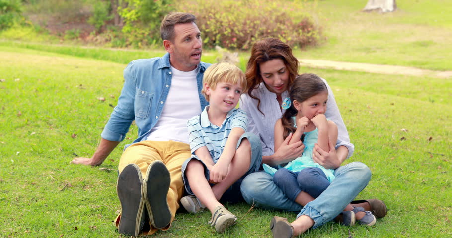Happy family sitting on grass in park | Shutterstock HD Video #11457206