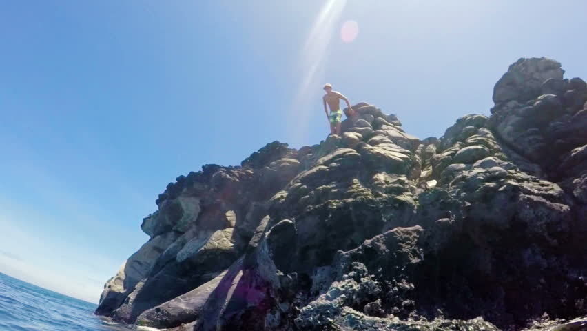 GOPRO POV of Athletic Young Man Jumping from Sea Cliffs into the Blue Ocean in Hawaii. Outdoor Active Lifestyle. SLOW MOTION