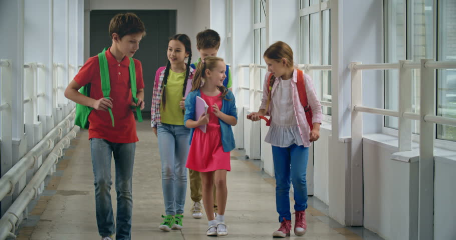 group of elementary students talking while walking down