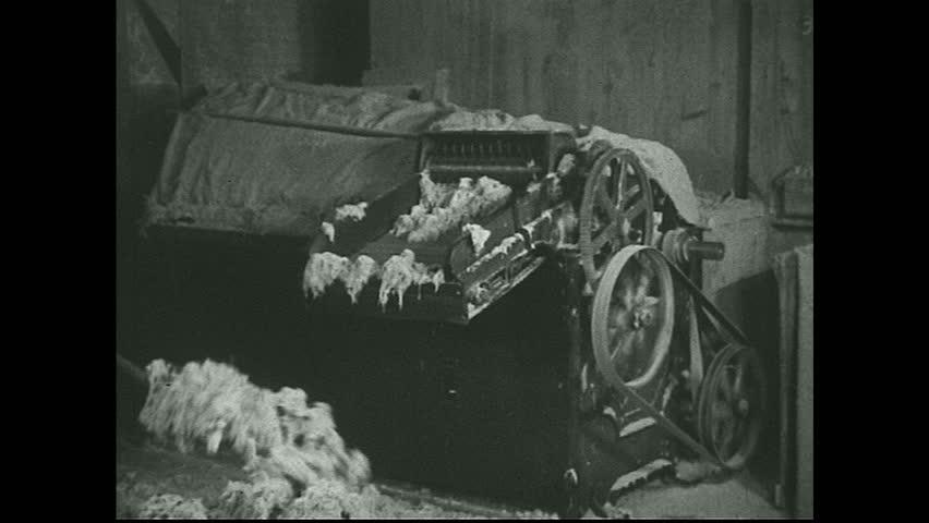 UNITED STATES 1930s - Men shovel raw asbestos material into mill. Mill processes fibers.