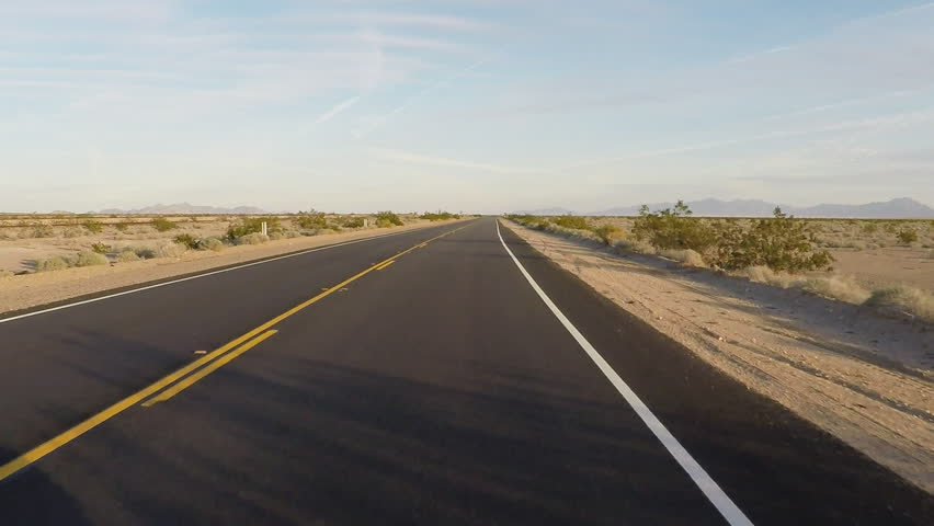Point of view vehicle driving shot of California Highway 62 through the Mojave desert. Viewpoint of driver over smooth blacktop asphalt on a stretch of desert highway. | Shutterstock HD Video #11596064