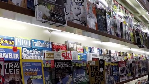 Coquitlam, BC, Canada - October 26, 2014 : Close up hand choosing magazine at London drugs store with wide angle camera shot