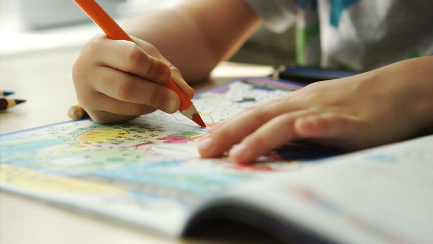 Child hands paints a colored pencils on a paper