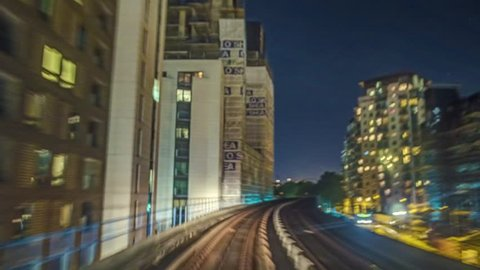 Time lapse of the Docklands in London in motion from a fast moving train at night, technique called hyperlapse