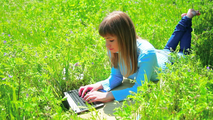 Lady on the field and works at laptop. Dolly work profile.