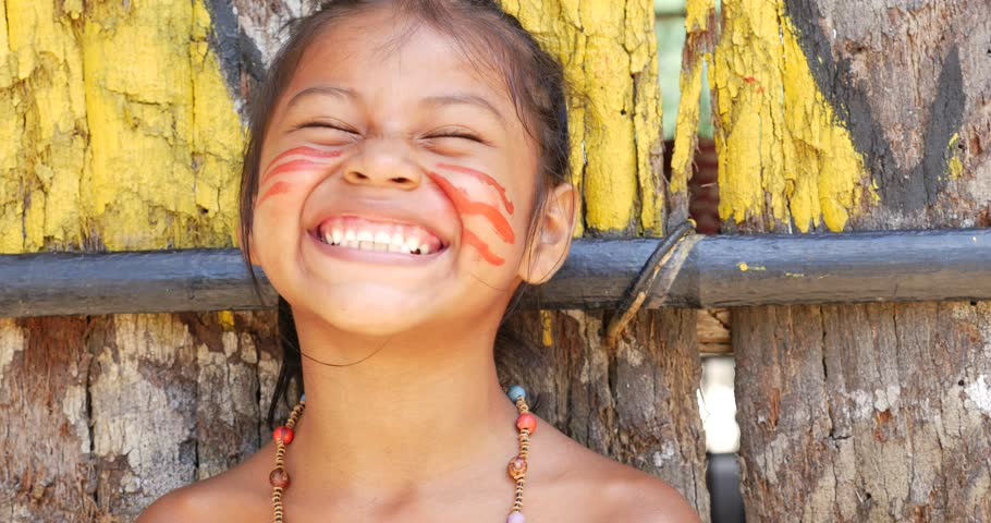 Cute native Brazilian girl smiling at an indigenous tribe in the Amazon