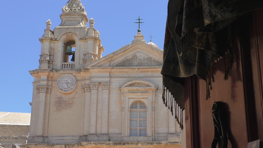 Light breeze moving a shawl or cloth with tassels hanging on the old open door with door knocker and St.Paul's church front with crosses in the background in Malta island,Mdina city