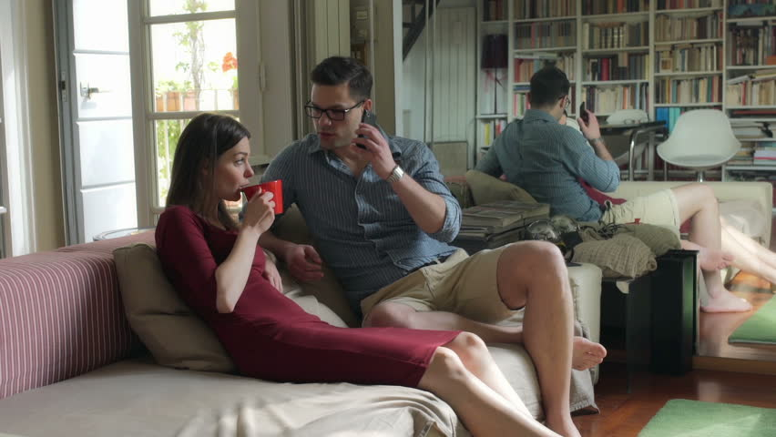 Couple sitting on the sofa and man talking on cellphone  | Shutterstock HD Video #11816456