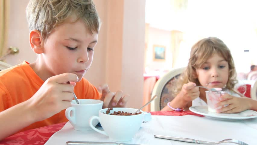 Boy and girl with curly hair eat granola and yogurt for breakfast