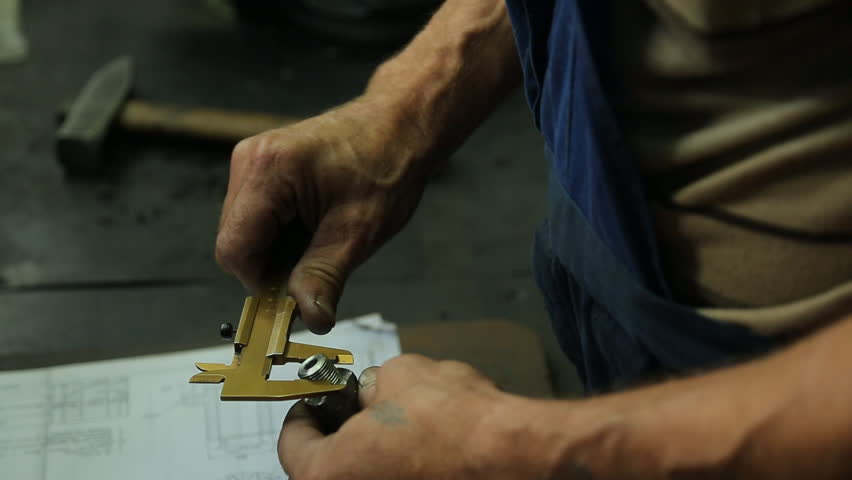 close up of a man checking the accuracy of the technique of manufacturing the two products, he is at his workplace, he discovered records on the details in the hands of a tool