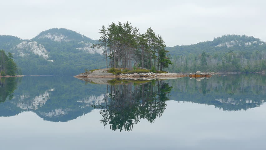 Drifting past island with stand of trees on calm lake with glass like surface in Killarney provincial park in Ontario, Canada. OSA Lake. Shot taken from canoe.