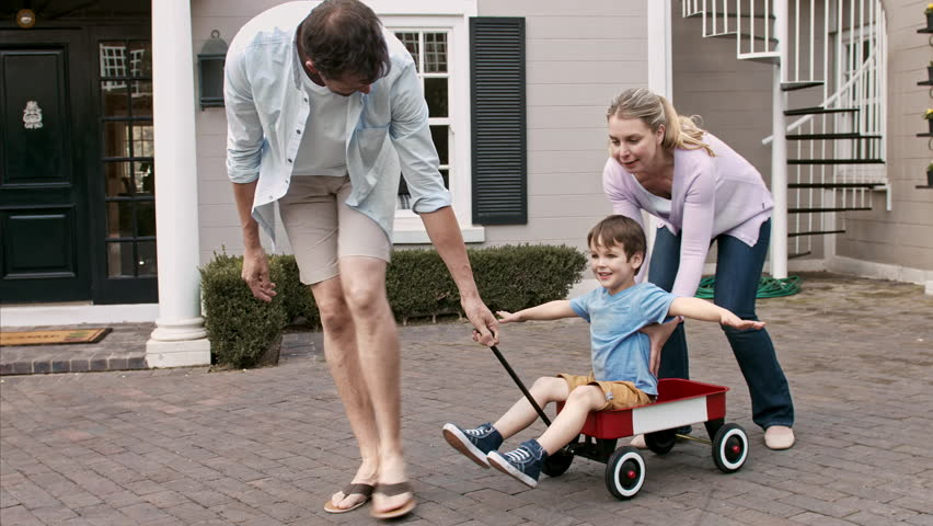 4k wide shot of father and mother pulling son as he is flying like an airplane for the first time in a wagon on driveway.