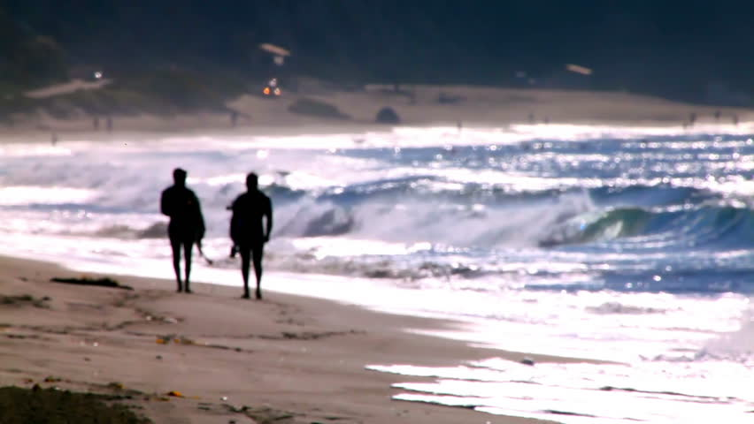 An out of focus shot of two surfers walking on a beach.