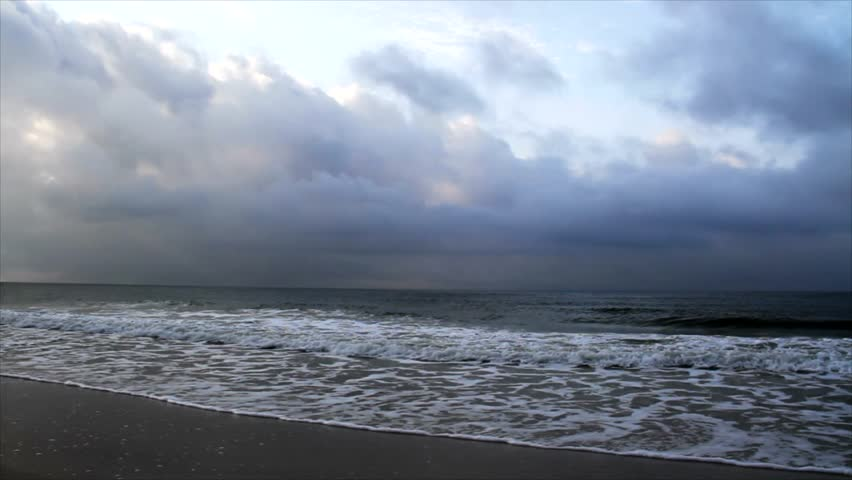 Sunlight shines on morning clouds over ocean waves on a sandy beach in this moody motion loop video.