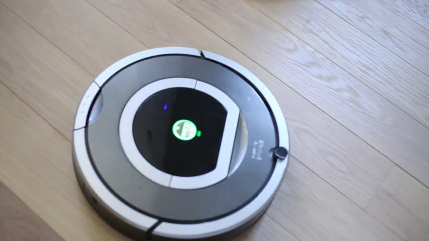 MOSCOW - OCT 30, 2014: Round electronic iRobot cleaner on floor. Company iRobot Corporation was founded in US in 1990
