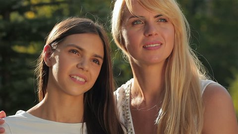 A mother and her teenage daughter look far away, each other and kiss. Happy mother with her daughter in park outdoors. Teenage girl outdoor with her mom. Portrait of mother with teenager daughter.