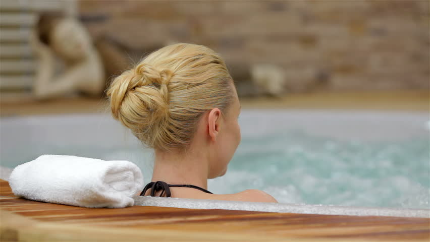 Back view of a woman enjoying Jacuzzi. Back view of a young woman enjoying Jacuzzi in a spa center. Happy woman relaxing in jacuzzi. Woman in spa salon.