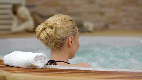 Back view of a woman enjoying Jacuzzi. Back view of a young woman enjoying Jacuzzi in a spa center. Happy woman relaxing in jacuzzi. Woman in spa salon.