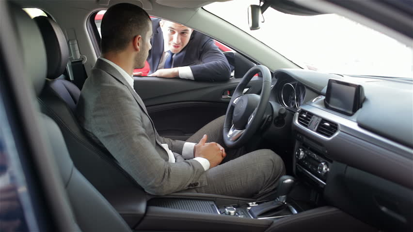Young man sitting in car. Auto business, car sale, technology and people concept - happy male with car dealer in auto show or salon. Young man with a salesman in a motor show. | Shutterstock HD Video #11918870
