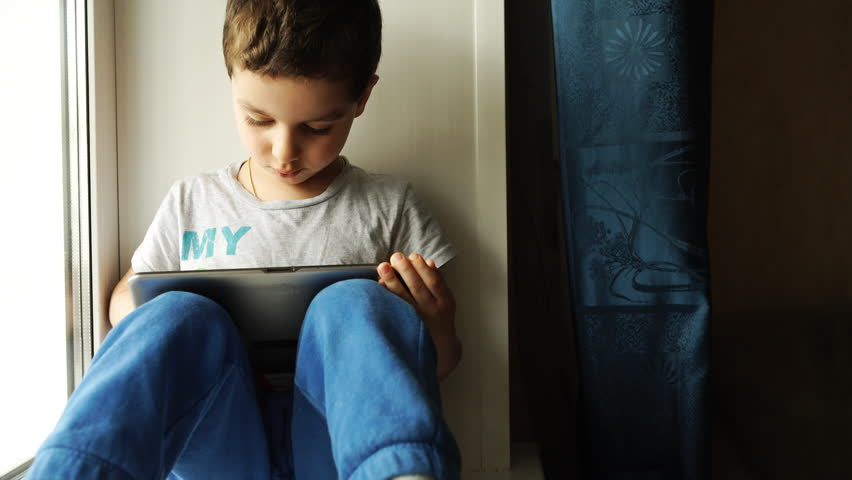 Child sits on a windowsill and uses a digital tablet pc