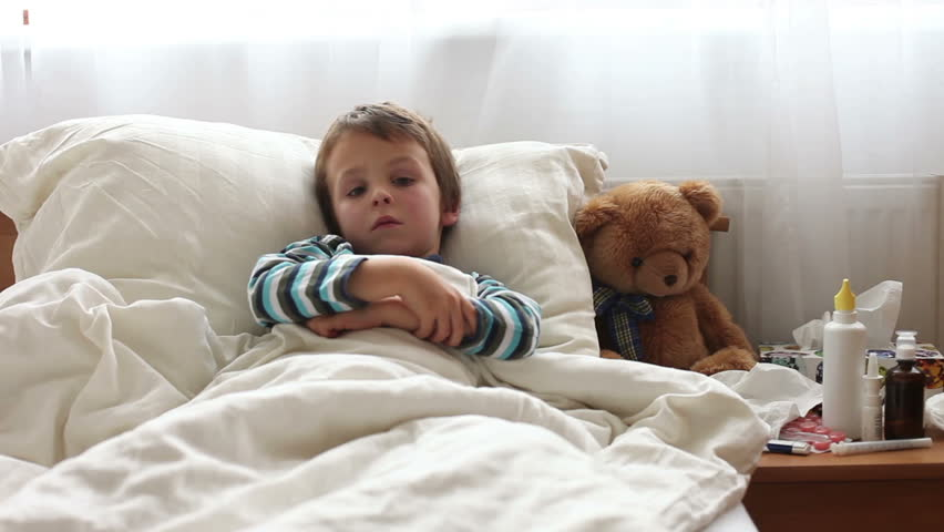 Sick child boy lying in bed with a fever,resting, coughing and blowing his nose