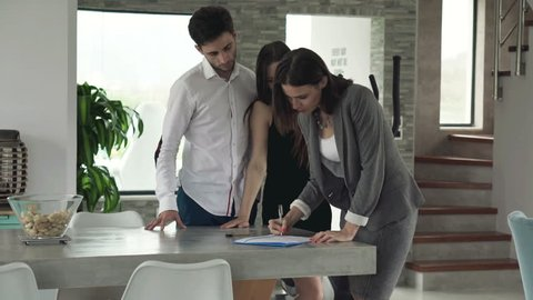 Real estate agent sign contract and giving home keys to happy couple