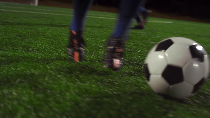 A female soccer player dribbles down the field during a game at night | Shutterstock HD Video #11951426