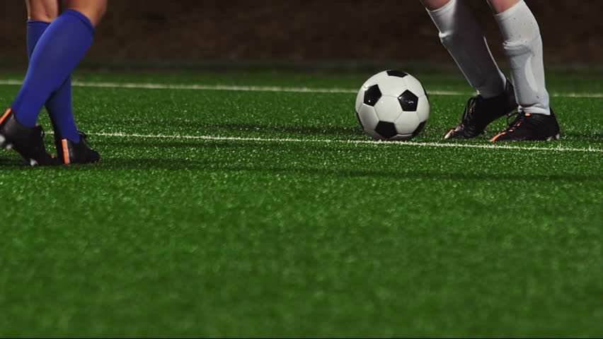 Close up of female soccer players dribbling down the field at night #11951456