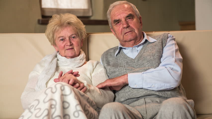 Elderly couple on sofa caressing looking of camera 4K. Old married grandparents enjoying time together at home on sofa sitting together, grandma caressing husband hand. Retro clothes.