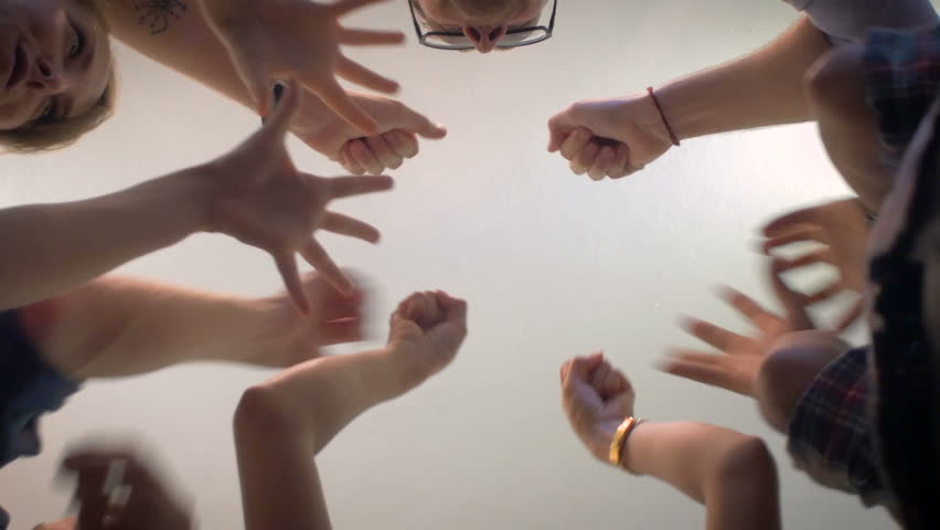 Low angle shot from below of a group of 5 young millennials place their hands together in the center of a circle and then cheer in a celebration of a successful event and shake hands and fist bump. #11970596