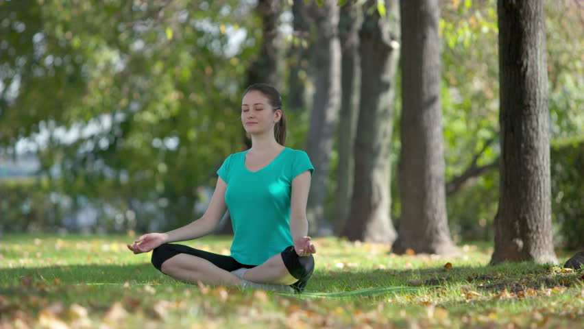 Beautiful young model woman practicing yoga in the Park,early autumn,Sunny day, Dolly shot