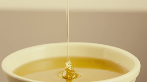 Honey pouring from dipper to bowl slow motion tilt down.100fps-25fps slow motion close up tilt down shot of honey dripping from a dipper,on to a bowl filled with honey.