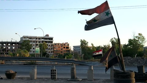 Disheveled Syrian flag at the entrance near the road to Damascus, Syria, September 2013